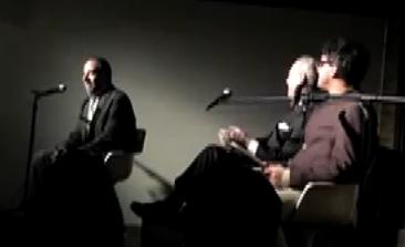 Debate stage showing Dean Baker, Jeffrey Tucker, and James Henry